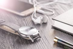 Armbanduhr, Handy mit Kopfhörern und ein Notizblock mit einem Stift auf einem alten dunklen Bürodesktop stockfotografie