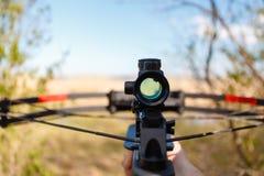 Armbrust des optischen Anblicks, die von der ersten Person auf dem Hintergrund des Sees zielt Lizenzfreie Stockfotos