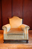 Armchair. Old antique beige armchair against wood panel wall Royalty Free Stock Photo