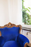 Armchair. Old fashioned blue armchair by the window stock photography