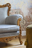 Armchair. Vintage fashioned gray chair in front of the Old wall, close-up royalty free stock photos
