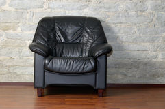 Armchair. View of a comfortable black leather armchair by an old limestone wall. Clipping paths with the chair&floor and with the chair only, included Stock Image