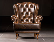 Armchair. Brown leather armchair on a black background Stock Photos