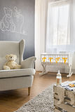 Armchair in baby room. Teddy bear on armchair in bright infant baby room Stock Photos