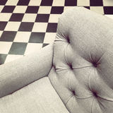 Armchair on black and white tile background Stock Images