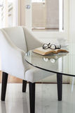 Armchair with book and eyeglasses on table Interior decoration Stock Image