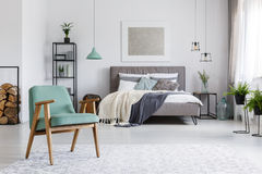 Armchair on carpet. Wooden mint armchair standing on a bright carpet in cozy room with bed stock image