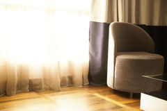 Armchair close to the window Royalty Free Stock Images