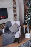 Armchair in a cozy Christmas interior with a fireplace, wood and a Christmas tree. Armchair in a cozy Christmas interior with a fireplace and wood Stock Photo