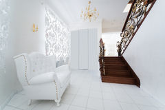 Armchair in the hallway. White armchair in the hallway with a staircase Royalty Free Stock Photo