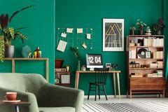 Armchair in home office. Close-up of armchair in home office interior with desk, bookshelf and green walls Stock Image