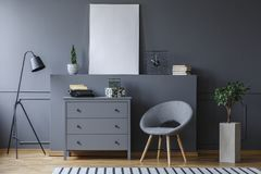 Armchair next to cabinet in grey living room interior with mockup of poster and lamp. Real photo royalty free stock images