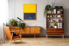 Armchair next to wooden cupboard with plants in retro flat interior with painting. Real photo royalty free stock image