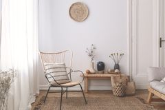 Armchair with pillow on brown rug in white natural living room interior with plants. Real photo. Concept stock images