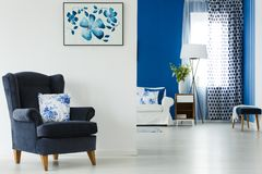 Armchair with pillow. Armchair with flowery pillow in blue and white living room royalty free stock image