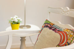 Armchair With Pillow. An armchair With Pillow nex to to a nightstand with flower vase Royalty Free Stock Photography