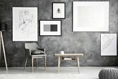 Armchair and table. Grey armchair with pillow and wooden coffee table with mug and books standing in simple room interior with posters stock photo