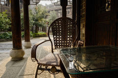 Armchair and tea-table in shaded veranda of traditional building Stock Image