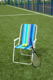Armchair, tennis racket and four balls on court Royalty Free Stock Photo