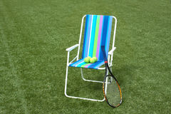 Armchair, tennis racket and four balls on court Royalty Free Stock Photos