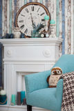 Armchair in Turquoise colors near a fireplace. And vintage clock under it Stock Image
