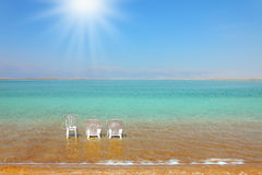 The armchairs and a chair in the clear water Royalty Free Stock Photography
