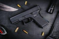 Arme à feu, couteau et cartouches sur une table noire Photographie stock libre de droits