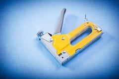 Arme à feu d'agrafeuse sur le concept bleu de construction de fond Photographie stock