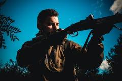 Arme à feu de chasse Chasseur visant le fusil dans le chasseur de forêt avec l'arme à feu de fusil de chasse sur la chasse Carabi photos stock