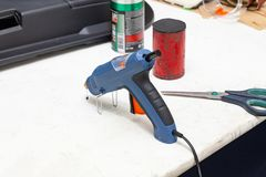 Arme à feu de colle électrique pour serrer la colle bleue sur l'établi pour la couture dans l'atelier à côté des ciseaux et la ma image libre de droits