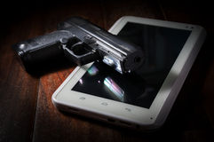 Arme à feu de main sur le comprimé d'ordinateur image stock