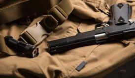 Arme à feu et torche sur le matériel brun Image stock