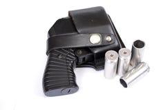 Arme à feu traumatique de quatre-remplissage non chargée dans un étui en cuir et les cartouches se trouvant tout près sur un fond image stock