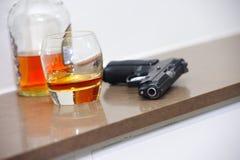 Arme à feu, verre, bouteille sur la table Images stock