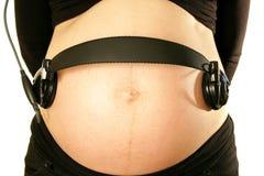 Arme auf schwangerer Mama blähen den Bauch auf, der Kopfhörermusik für b hält Stockbild