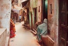 Arme Leute in den langen traditionellen Schals, die auf der Schmutzstraße der alten indischen Stadt sitzen Lizenzfreie Stockfotografie