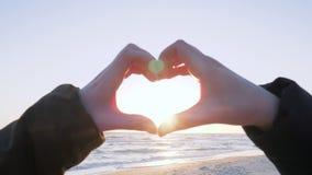 Arme von Leuten machen Herz gegen Himmel bei Sonnenuntergang auf Küste stock video footage