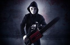 Armed assassin in an empty bloody room concept. Armed rude assassin in an empty bloody room concept with gun ax chainsaw mallet wrenchn royalty free stock photo