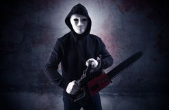 Armed assassin in an empty bloody room concept. Armed rude assassin in an empty bloody room concept with gun ax chainsaw mallet wrenchn royalty free stock photos