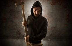 Armed assassin in an empty bloody room concept. Armed rude assassin in an empty bloody room concept with gun ax chainsaw mallet wrench royalty free stock photos