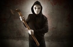 Armed assassin in an empty bloody room concept. Armed rude assassin in an empty bloody room concept with gun ax chainsaw mallet wrench stock photography