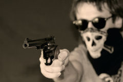 Armed assault. A masked man in sun glasses armed with a hand gun Royalty Free Stock Image