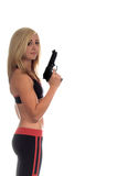 Armed and Beautiful. Beautiful blond personal trainer armed with a 45 caliber semi automatic handgun royalty free stock photography