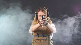 Armed blonde woman shoots with gun at a target in the darkness with smoke clouds. Slow motion. Armed beautiful blonde woman wearing protective headphones and stock video footage