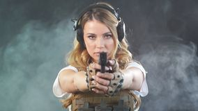Armed blonde woman shoots with gun at a target in the darkness with smoke clouds. Slow motion. Armed beautiful blonde woman wearing protective headphones and stock footage