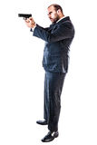 Armed Bodyguard. Portrait of a classy businessman or mobster or security guard holding a gun isolated over a white background royalty free stock photography