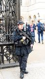 Armed British Policewoman Standing Guard. Armed policewoman with sub-machine gun and taser stands guard in England London stock photos