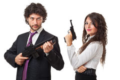 Armed for business. A businessman and a businesswoman (or maybe a couple of spies or gangster) holding guns over a white background stock photo