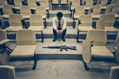 Armed campus. A man with a pistol and a rifle in a lecture room / Armed campus concept stock photo