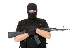 Armed criminal. Portrait of violent killer holding firearm and looking at camera with balaclava on his head Royalty Free Stock Photography